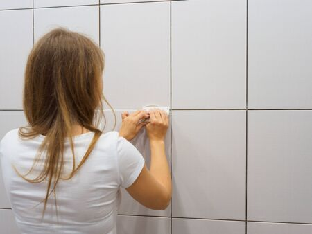 Girl covers the joints with putty in the bathroom. Repairs.