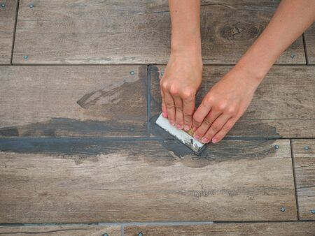 Grouting between ceramic tiles. Female hands hold a spatula. Repair in the room Stock Photo