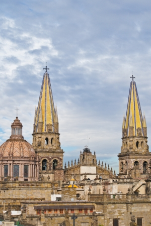 Yellow Steeples Tower Above a  Cathedral in Guadalajara Mexico