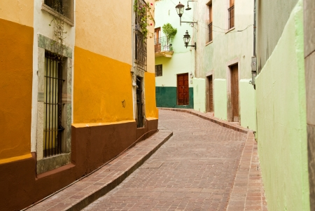 Colorful buildings line a narrow cobblestone street in romantic Guanajuato Mexico Stock Photo
