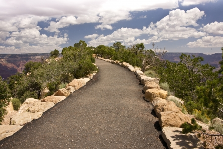 A paved walkway leads to the precipice overlooking the Grand Canyon Stock Photo