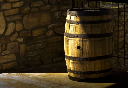 Sunlight illumintaes an old woodnen barrel beside a stone wall Stock Photo