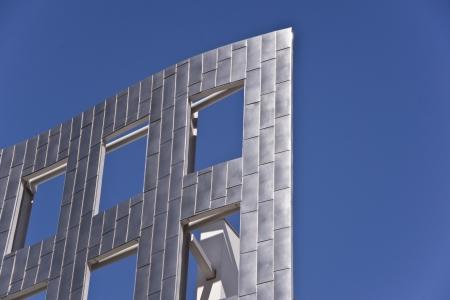 Blue sky shines through windows and gleaming metallic building facade Stok Fotoğraf
