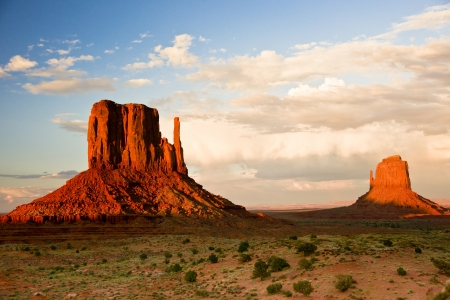 Massive sandstone pillars soar above iconic Monument Valley at sunset photo
