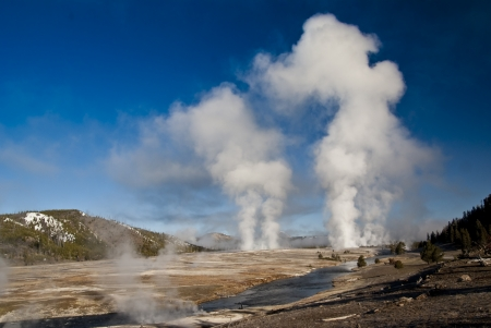 Steam billows from geysers in Yellowstone Park photo