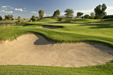 Gaping sand traps and a pond, fram the green on a lush desert golf course in mid-summer