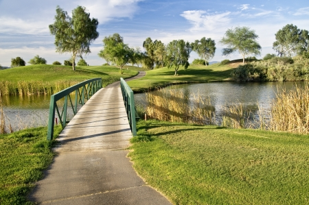 water feature: Pedestrian bridge over a small pond at a golf course as sunset nears