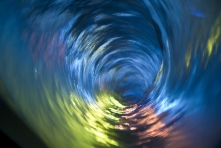 Looking down into a swirling multi-colored water vortex