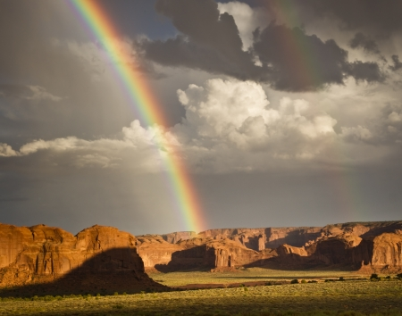 Brilliant double rainbows arch above Monument Valley