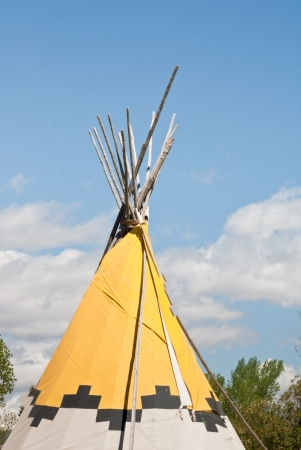 plains indian: The peak of a plains Indian teepee is highlighted against the azure Montana sky Stock Photo