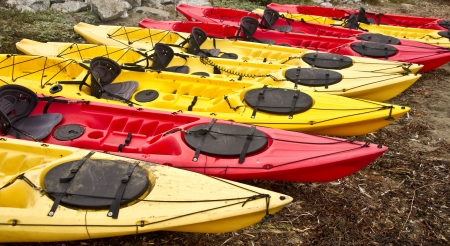 Vividly colored seak kayaks sit on the beach at a California cove Stock Photo