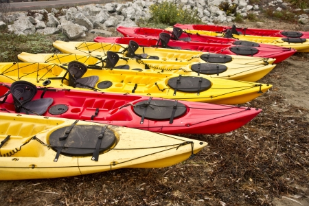 Vividly colored seak kayaks sit on the beach at a California cove Stok Fotoğraf