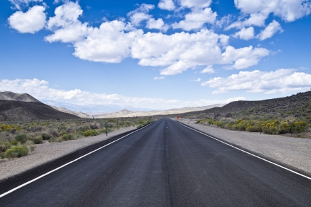 A vast expanse of open highway stretches across the Nevada desert north of Las Vegas