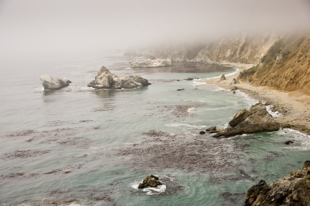 Ocean fog shrouds the steep cliffs along the Big Sur coastline
