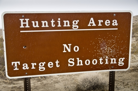 A sign blasted by a shotgun warns hunters that they must shoot to kill - no more practicing photo