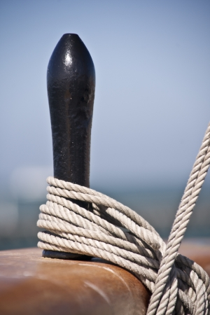 belay: Close up of a wooden cleat used to tie-off or belay rigging cordage on a sailing ship Stock Photo