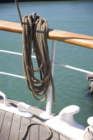 cordage: Close up of a wooden cleat used to tie-off or belay rigging cordage on a sailing ship Stock Photo