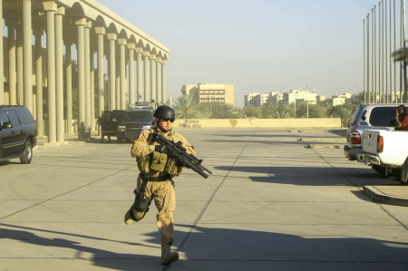 A heavily-armed operator from Blackwater USA sprints into position as an incoming helicopter approaches an exfiltration site for a diplomatic meting in Baghdad, circa December 2006