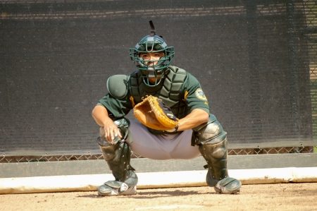 A basebal catcher prepares to receive the pitch during MLB spring training practice and tryouts