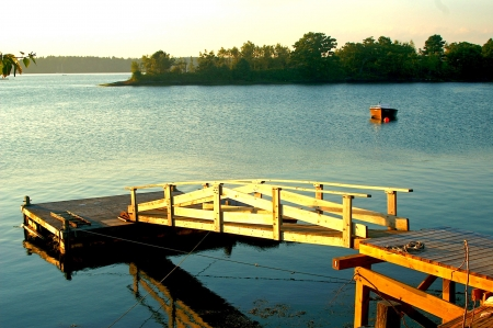 Late afternoon light shines on a wooden dock on a small bay along the Maine coast in summer  photo