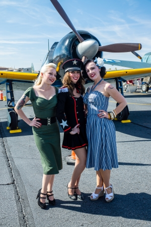 Bullhead City, USA - April 6, 2013  Gals from the Pinup Patriettes pose in period fashion with vintage World War II warplanes at the Legends Over the Colorado air show  版權商用圖片 - 19256982