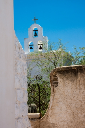 The bells of San Xavier del Bac mission contrast with blue sky and whitewashed architecture