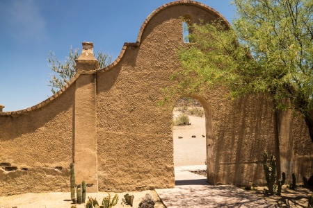 An arched wall and entry to Mission San Xavier shows the distinctice Spanish colonial influence of the architecture  Stock Photo
