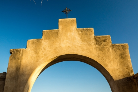 An iconinc adobe arhway and crucifix at a Spanish mission in Arizona Stock Photo