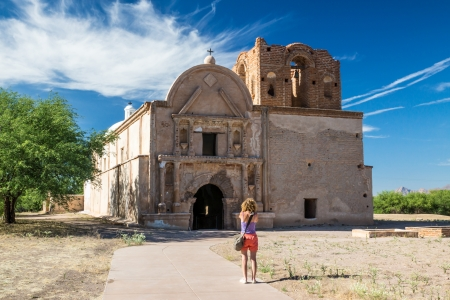jesuit: A woman visitor take a picture of the preserved Spanish mission at Tumacacori, Arizona Stock Photo