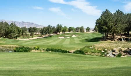A lush fairway in the foreground contrast with harsh desert mountains in the distance at a golf course  Stock Photo