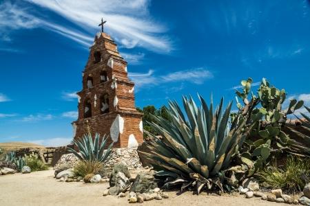 san miguel arcangel: El campanario de la histórica Misión de San Miguel Arcángel se encuentra con orgullo en medio de plantas de cactus bajo un cielo de verano hermoso en California