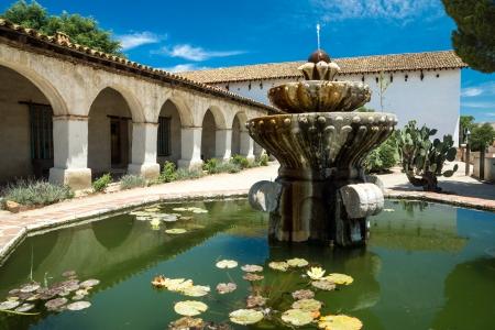 san miguel arcangel: Fuente con hojas de nenúfar junto a una columnata en una misión histórica California