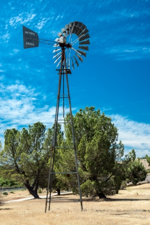 outpost: An iconic widnmill stands beneath the blue sky and wispy white clouds at an historic landmark in the far west of California