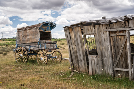 An old west sheriffs wagon sits on the lonesome frontier prarie as storm clouds gather in the distance.