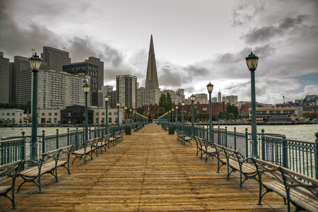 The San Francisco skyline from an old pier along the embarcadero in the bay, as a storm approaches. Stock Photo