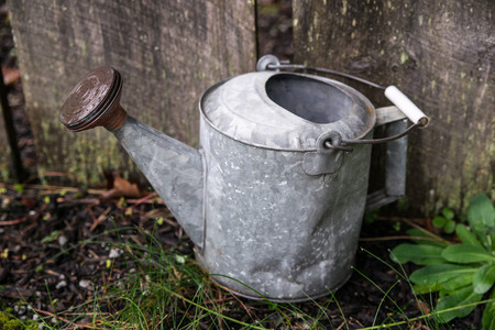 An old metal watering can sits beside a wooden fence.