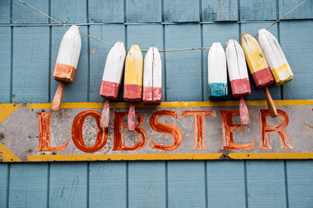 buoys: Buoys hang above a faded sign promoting losters