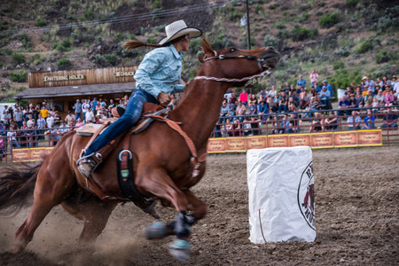 arena rodeo: Gardiner, MT, USA - June 20, 2015: A cowgirl guides her Quarter horse around a barrel in the barrel racing event at the annual Gardiner, Montana rodeo. Editorial
