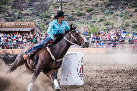 Gardiner, MT, USA - June 20, 2015: A cowgirl guides her Quarter horse around a barrel in the barrel racing event at the annual Gardiner, Montana rodeo. Editöryel