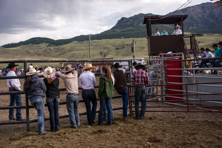 arena rodeo: Gardiner, MT, USA - June 20, 2015: Cowboys and cowgirls await the start of the annual rodeo in Gardiner, Montana under stormy skies. The rodeo offers visitors to nearby Yellowstone Park a glimpse into western lifestyles. Editorial
