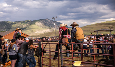 arena rodeo: Gardiner, MT, USA - June 20, 2015: The crowd of cowboys, cowgirls line the arena stockade during the annual western rodeo in Gardiner, Montana. The rodeo offers tourists to nearby Yellowstone Park a glimpse into western cultyre.