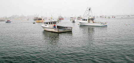 rowboats: Rye, NH, USA - August 20, 2015: Small boats lie at anchor as fog shrouds the quaint harbor in Rye, NH.