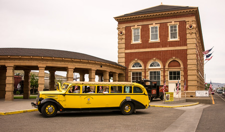 Livingston, MT, USA, June29, 2015: Tourists board a vintage historic yellow bus for a chartered excursion from the Livington Montana traind depot to Mammoth Hot Springs in Yellowstone Park.