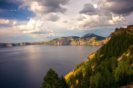 crater lake: Late afternoon light illuminates the shore of Crater Lake in Oregon.