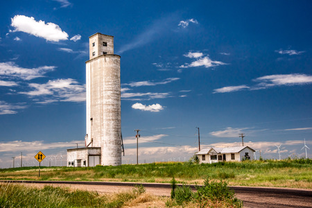 new economy: An old grain silo stands above a texas wind farm, contrasting the old and new economy.