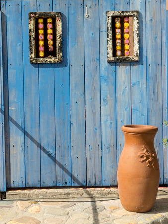 terra cotta: An old fashioned blue wooden door and rustic clay vase at a Mexican hacienda.