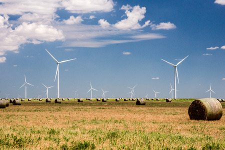 Wind turbines provide clean energy as they tower above a ranch and haystacks in Texas. Imagens