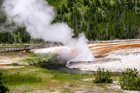 traverse: Wooden boardwalks traverse the surreal landscape at Black Sand Basin near Old Faithful in Yellowstone Park.