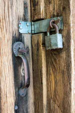 hinge: Doorway secured by a hinge, clasp, wrought iron handle and a pad;ock Stock Photo