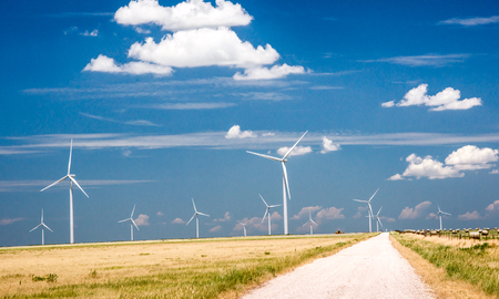 Wind turbines provide clean energy as they tower above a ranch and haystacks in Texas. Stock Photo